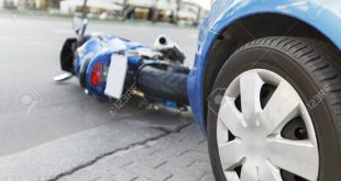 The accident blue bike with a blue car. The motorcycle crashed into the bumper of the car on the road. The motorcycle lies on the road near the car.